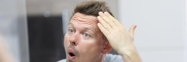 L'uomo narcisista davanti allo specchio si fa i capelli