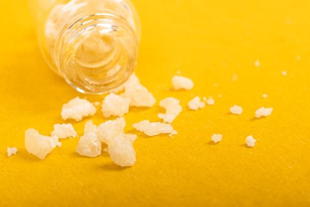 Anfetamina di cristalli di sale narcotico su sfondo giallo.