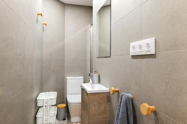 Bagno stretto con wc piccolo lavabo decorato con piastrelle grigie interni in stile contemporaneo dopo...
