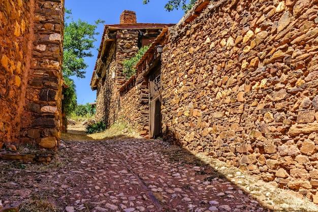 Stretta strada acciottolata con rustiche case in pietra e atmosfera antica e medievale.