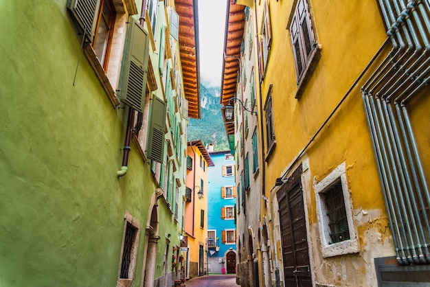 Strade strette e colorate in un tipico villaggio italiano ai piedi delle montagne.