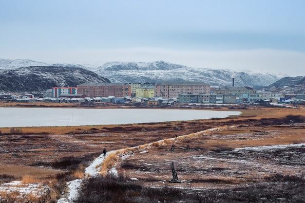 Uno stretto sentiero che porta in lontananza al villaggio artico situato tra le colline polari.