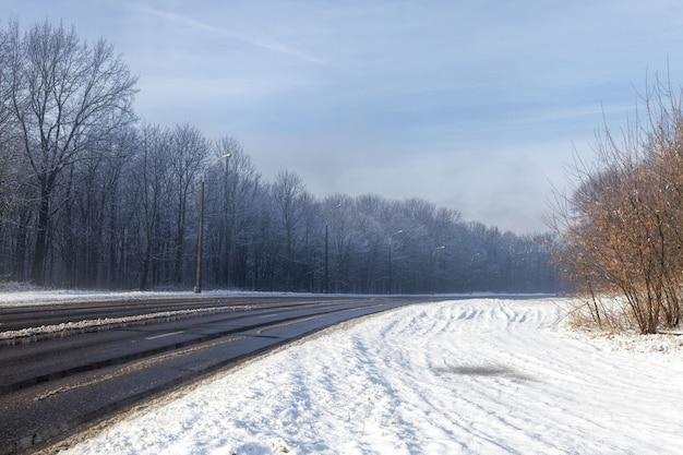 Stretta strada invernale asfaltata coperta di neve per il traffico automobilistico
