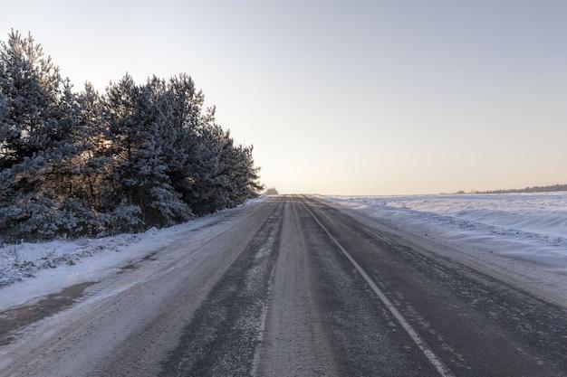Stretta strada invernale innevata per guidare auto attraverso la foresta, cielo nuvoloso sulla strada, neve sulla strada si accartoccia e si scioglie dal movimento delle auto