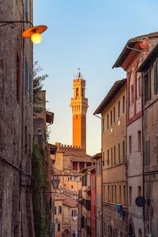La stretta strada che conduce a piazza del campo e torre del mangia a siena, italia.