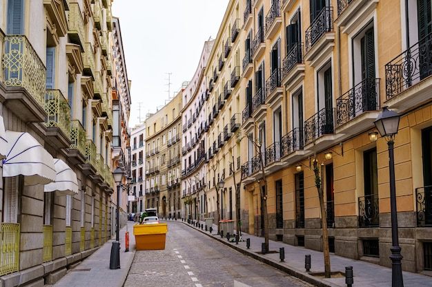 Strada stretta a madrid con balconi tipici della città ed edifici colorati. spagna.