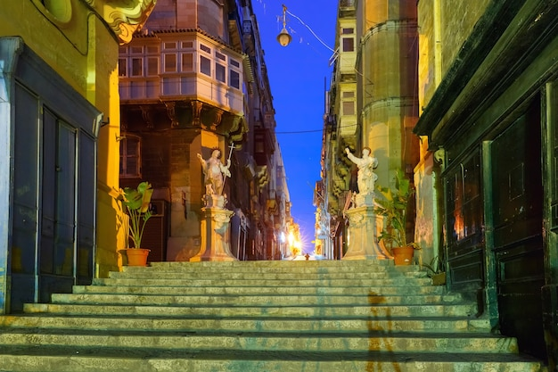 Scale strette con angoli di case, decorate con statue di santi di notte nella città vecchia di la valletta, malta