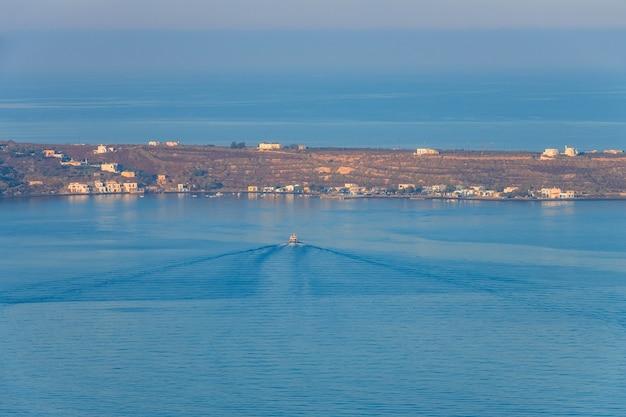 Stretta striscia di costa senza alberi. una barca a motore galleggia al molo in acque tranquille. vista aerea