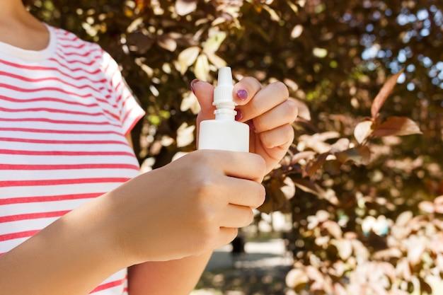 Flacone per gocce nasali, spray nasale per spruzzatura a mano femminile con sfondo sfocato.