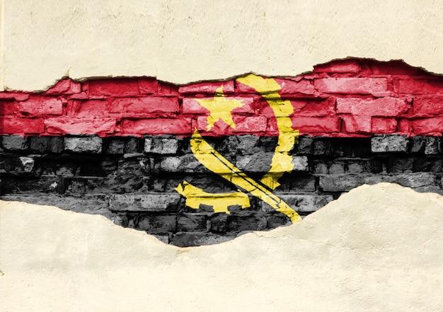 Bandiera nazionale dell'angola su uno sfondo di mattoni. muro di mattoni con intonaco parzialmente distrutto, sfondo o texture.
