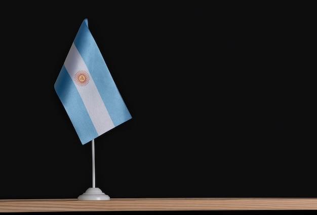 Bandiera nazionale dell'argentina sul tavolo su fondo nero. asta bandiera.