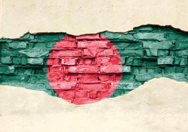 Bandiera nazionale del bangladesh su uno sfondo di mattoni. muro di mattoni con intonaco parzialmente distrutto, sfondo o texture.