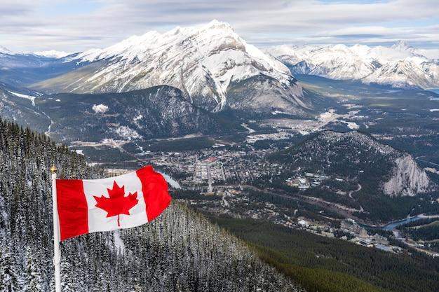 Bandiera nazionale del canada con montagne rocciose canadesi nel parco nazionale di banff invernale canada