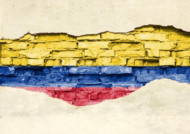 Bandiera nazionale della colombia su uno sfondo di mattoni. muro di mattoni con intonaco parzialmente distrutto, sfondo o texture.