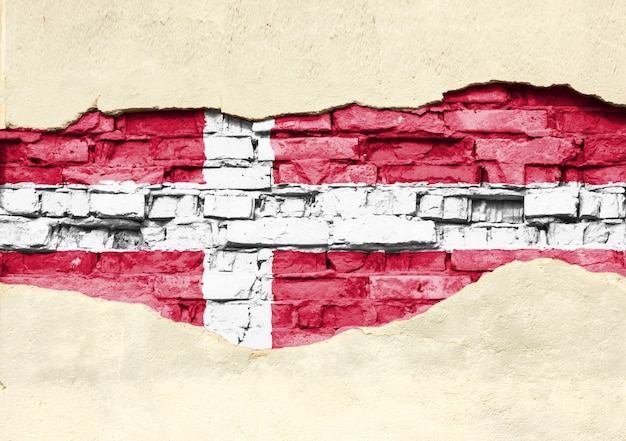 Bandiera nazionale della danimarca su uno sfondo di mattoni. muro di mattoni con intonaco parzialmente distrutto, sfondo o texture.