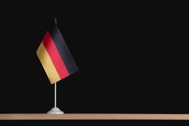 Bandiera nazionale della germania sul tavolo, sfondo nero. bandiera tricolore di nero, rosso, giallo. copia spazio.