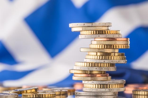 Bandiera nazionale della grecia e delle monete in euro - concetto. monete in euro. soldi dell'euro. valuta dell'euro.