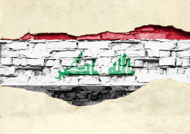 Bandiera nazionale dell'iraq su uno sfondo di mattoni. muro di mattoni con intonaco parzialmente distrutto, sfondo o texture.