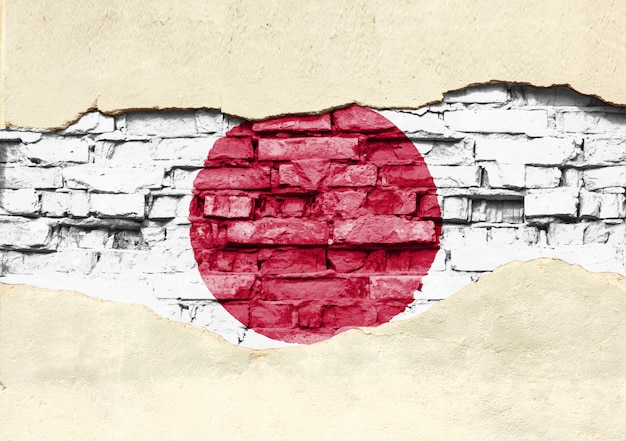 Bandiera nazionale del giappone su uno sfondo di mattoni. muro di mattoni con intonaco parzialmente distrutto.