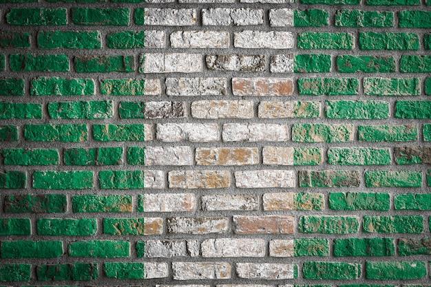 Bandiera nazionale della nigeria su un vecchio muro di mattoni
