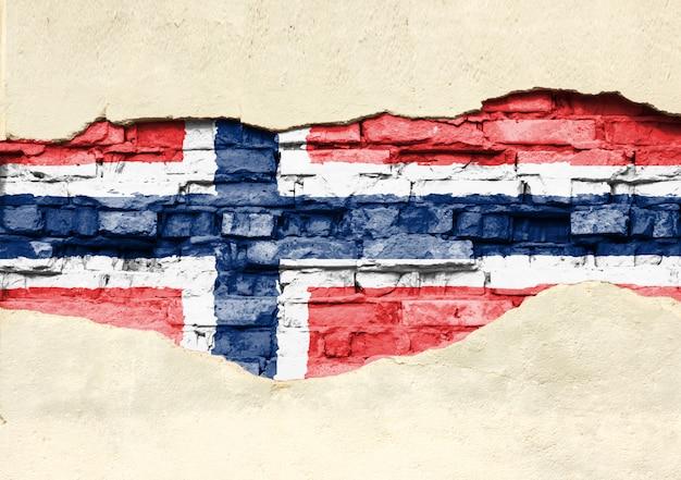 Bandiera nazionale della norvegia su uno sfondo di mattoni. muro di mattoni con intonaco, fondo o struttura parzialmente distrutti.