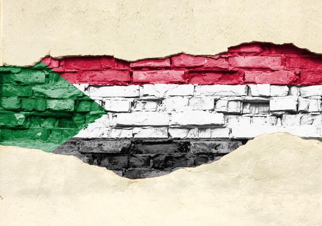 Bandiera nazionale del sudan su uno sfondo di mattoni. muro di mattoni con intonaco parzialmente distrutto, sfondo o texture.