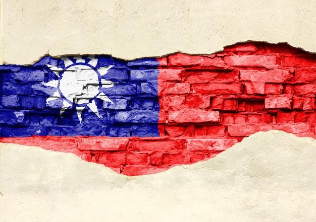 Bandiera nazionale di taiwan su uno sfondo di mattoni. muro di mattoni con intonaco parzialmente distrutto, sfondo o texture.