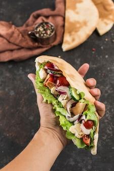 Pita greca nazionale degli alimenti a rapida preparazione con pollo e verdure fresche nella mano maschio dello chef su uno sfondo scuro, vista dall'alto. orientamento verticale.