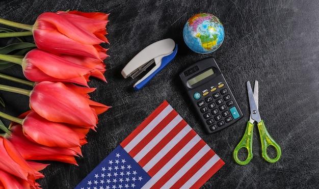 Festa nazionale. mazzo di tulipani, materiale scolastico e bandiera degli stati uniti su una lavagna. di nuovo a scuola