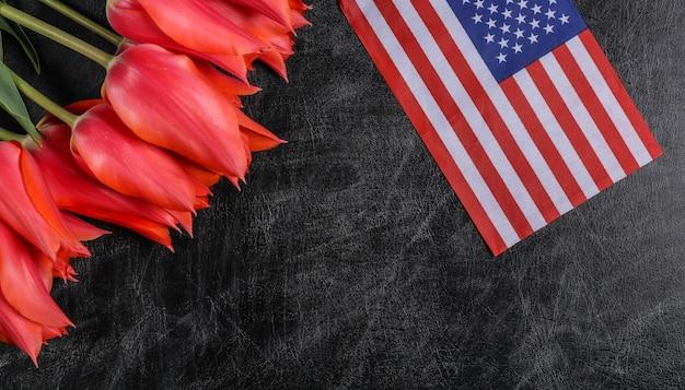 Festa nazionale. mazzo di tulipani e bandiera degli stati uniti su una lavagna. di nuovo a scuola