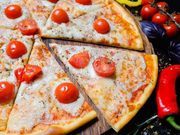 Pasto nazionale italiano. deliziosa fetta di pizza con formaggio fuso e pomodorini