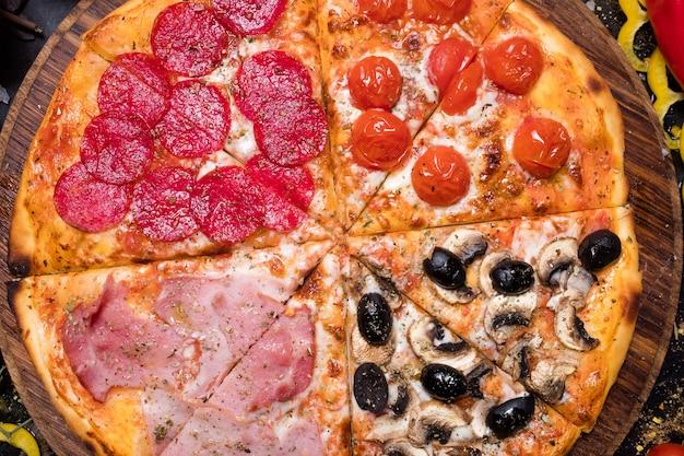 Pasto nazionale italiano. pizza fatta in casa con quattro stagioni prosciutto crudo pomodori olive e funghi. cibo gustoso e nutriente