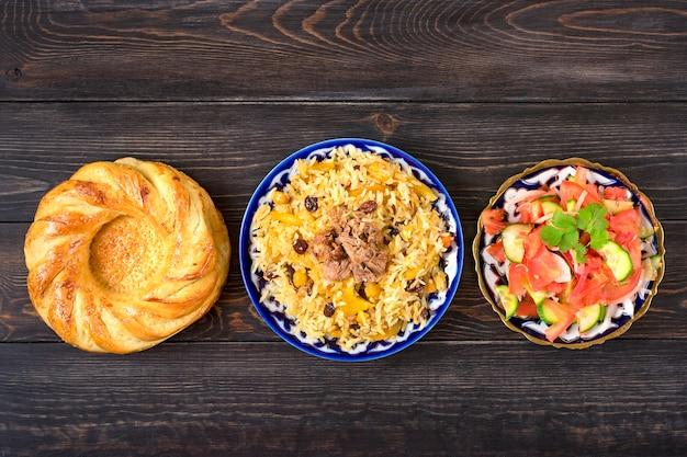 Pilaf nazionale uzbeko con carne, insalata di achichuk di pomodoro, cetriolo, cipolla in zolla con tradizionale