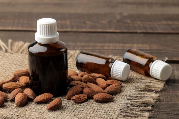 Olio cosmetico di mandorle naturali in una bottiglia di vetro e noci di mandorle fresche close-up su un tavolo di legno marrone.