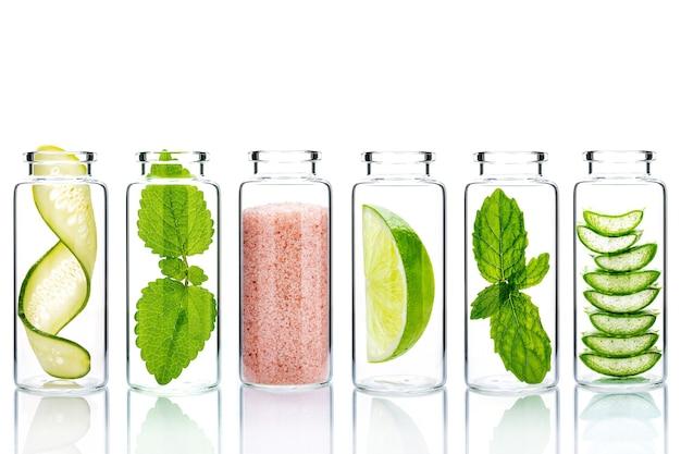 Ingredienti alternativi naturali per la cura della pelle in bottiglie di vetro isolare su sfondo bianco.