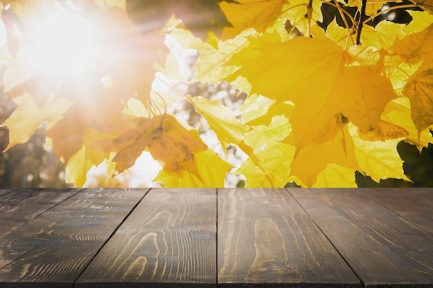 Estratto naturale di autunno con il ripiano del tavolo di legno per visualizzare il vostro prodotto.