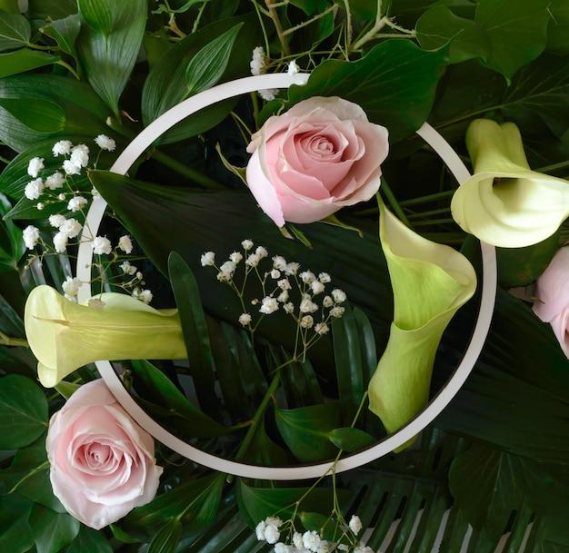 Sfondo naturale con una combinazione di diversi tipi di foglie, palme tropicali e fiori rosa e calla lilly con cornice circolare