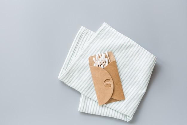 Accessori per il bagno naturali: bastoncini per le orecchie e asciugamano facciale su fondo di carta grigia.