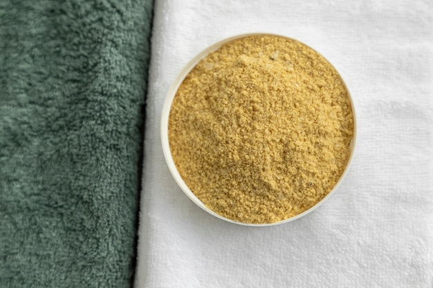 Scrub naturale per il corpo su asciugamani bianchi ed eucalipto.