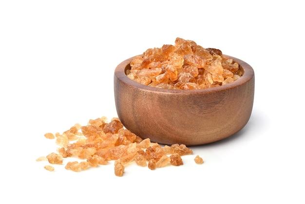 Zucchero di roccia marrone naturale ottenuto dalla canna da zucchero in una ciotola di legno isolato su priorità bassa bianca.