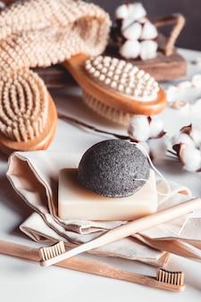 Spazzole naturali in legno e sapone sullo sfondo di cemento, spazzolini da denti in bambù e spazzola per il corpo, sapone fatto a mano con luffa