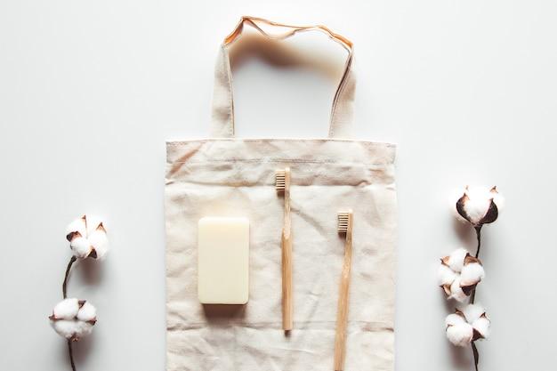 Spazzole naturali in legno e sapone sullo sfondo di cemento, spazzolini da denti in bambù e spazzola per il corpo