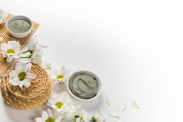 Maschera di argilla naturale asciutta e bagnata con fiori su sfondo bianco