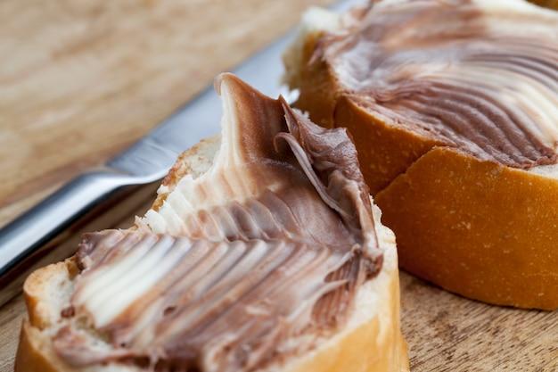 Pasta di cioccolato al cacao naturale durante la colazione, fette di pane bianco con crema di burro dolce al cioccolato, burro morbido al cioccolato e pane bianco
