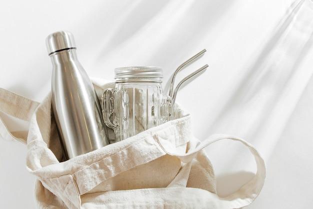 Borsa ecologica in colore naturale con borraccia in metallo riutilizzabile, barattolo di vetro e cannuccia. zero sprechi.