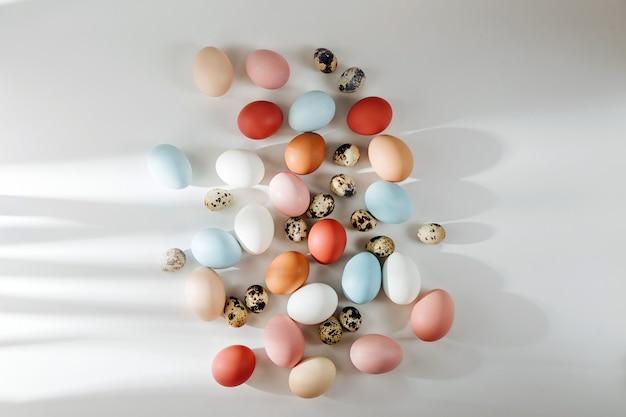 Colore naturale marrone, quaglia e uova bianche con i raggi del sole. composizioni in colori pastello. concetto di pasqua. disposizione piatta, vista dall'alto
