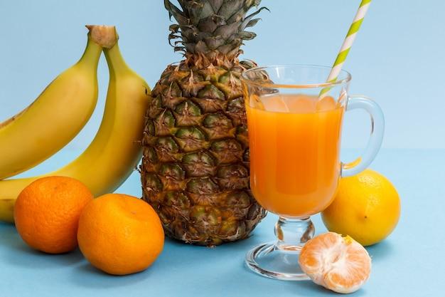 Composizione naturale con frutti tropicali. ananas fresco, banane, mandarini e un limone con un bicchiere di succo di frutta sullo sfondo blu.