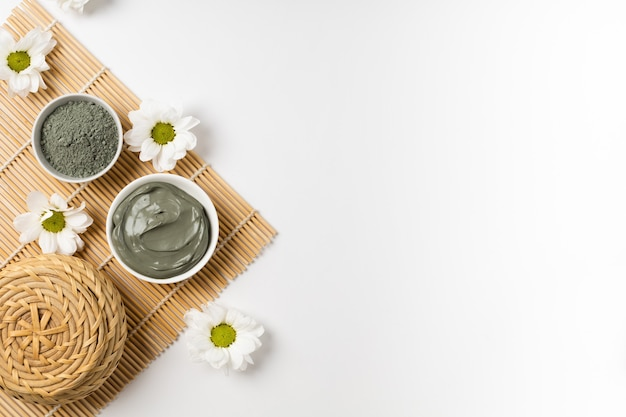 Argilla cosmetica naturale in ciotole e con fiori su stuoia di bambù per salone spa