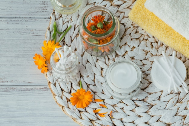 Crema cosmetica naturale, balsamo o unguento, dischetto di cotone, bastoncini e asciugamani con fiori secchi e freschi di calendula.