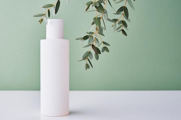 Bottiglia di crema cosmetica naturale su sfondo verde con pianta